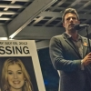 Ben Affleck as murder suspect Nick Dunne beside a poster of missing wife Amy Dunne, played by Rosamund Pike